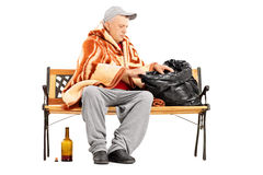 Homeless mature man sitting on a bench and looking for something Royalty Free Stock Photos