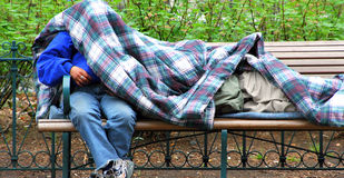 Homeless men. Homeless men sleeping outside in the cold on a park bench after losing their jobs to the tough economy Royalty Free Stock Images
