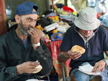 Homeless men eating Stock Photos