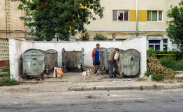 Homeless men searching in garbage container leftovers. BUCHAREST, ROMANIA - JUNE 26, 2014: Homeless men searching for food or usefull things in garbage dumpster Stock Photo
