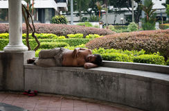 Homeless men sleeping in a park. KUALA LUMPUR - JUN 15: Homeless men sleeping on a bench in a public park on a midday on Jun 15, 2013 in Kuala Lumpur, Malaysia Royalty Free Stock Photo