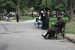 Homeless men and women  in a city park Stock Image