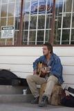 Homeless Musician. Hopeful homeless man singing & playing guitar for money Royalty Free Stock Image