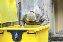 Homeless near garbage container Royalty Free Stock Photos