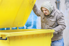 Homeless near garbage container Royalty Free Stock Photography