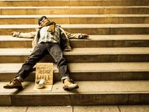Homeless man sleeping on stairs. A homeless old Asian man sleeping on a stairway begging for money Stock Photo