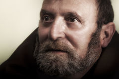 Homeless old man with beard looking forward. A homeless man looking forward with a sincere expression and almost serene, innocent. He is wearing a robe. Typical royalty free stock images