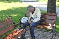 Homeless. Old homeless man sleeping on bench in Sibiu,Romania Royalty Free Stock Image