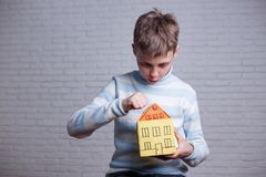 Homeless, orphan, settler, migrant, adoption concept. Boy knocki. Ng to cardboard toy house, dreaming about real home Stock Photos