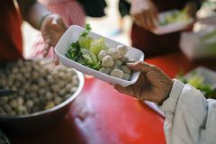 Homeless people are helped with food relief, famine relief : volunteers giving food to poor people in desperate need : The concept. Of food sharing Help solve royalty free stock images