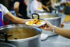 Homeless people pick up charity food from the food donors in society : concept homelessness.  royalty free stock images