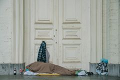 Homeless people sleeping in front of the Saint Jacques-sur-Coudenberg church royalty free stock photo