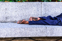 Homeless people sleeping at streetside in city Stock Photography