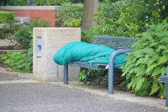 Homeless Person on City Bench. A homeless person sleeps on a city bench Stock Image