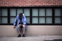 Homeless person sitting by the wall royalty free stock images