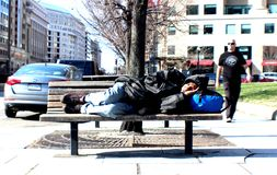 A homeless person sleep on the Chair by the street. Life is tough for homeless in Washington area stock photos