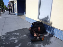 Homeless person sleep in shade of tree on sidewalk to avoid the Stock Photo