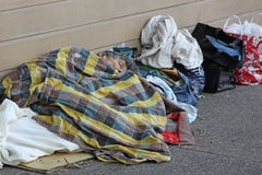 Homeless person sleeping on street. Covered by various pieces of fabric with shopping bags of possessions nearby Stock Image