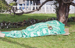 Homeless person sleeping under blanket in park royalty free stock photo