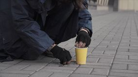 Beggar picking change. Homeless person taking coins from pavement on city street Stock Photos