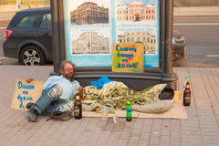 Homeless poor drunk man lying in the street. Homeless man lying in the street alms in Russia. Saint-Petersburg stock photo