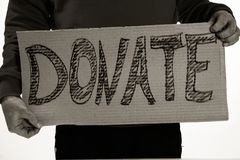 Homeless poor man holding carton board with word DONATE. For donations Royalty Free Stock Image