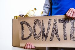 Homeless poor man holding carton board with word food DONATE. For donations Stock Photo