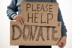 Homeless poor man holding carton board with word Please help, DONATE. For donations Stock Image