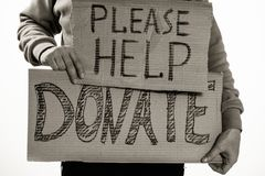 Homeless poor man holding carton board with word Please help, DONATE. For donations Stock Photos