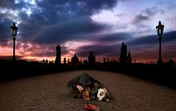 Homeless in Prague. Hooded young Man begging cuddles two Dogs for warmth on deserted Charles Bridge in Prague royalty free stock image