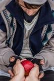 Homeless praying man. Homeless man is taking an apple. Antisocial element royalty free stock image