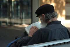 Homeless reading the bible. Homeless sitting on a bench and reading the bible royalty free stock photo
