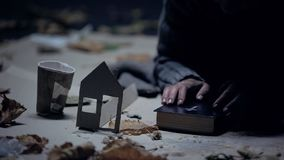 Homeless refugee holding bible, paper house and cup nearby, searching for home royalty free stock photos