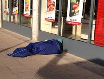 Homeless rough sleeper on the street. Great Britain. A homeless man rough sleeping outside a shop in a city in a  sleeping bag in Great Britain Stock Photography