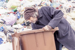 Homeless rummages in the dustbin of landfill Stock Image