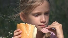 Homeless Sad Child in Abandoned House Unhappy Stray Girl Eating Bread Sausage royalty free stock image