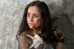 Homeless and scared. Homeless young woman dressed in rags in a derelict building Stock Photos