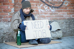 Homeless seated in the street and asking for a job Stock Image