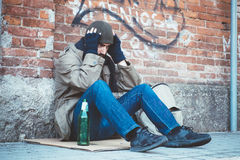 Homeless seated in the street and feeling desperate Stock Photography