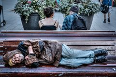 Homeless Senior Man Sleeping on Park Bench. A homeless man sleeps on a park bench in Montreal, QC, Canada. Homelessness has become a major concern in Canada. It Stock Photo
