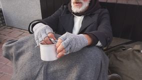 Homeless senior man wearing coat, suffering from cold weather meet rich man in street