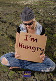 Homeless. Sitting on dry land is holding a piece of cardboard with the words Im hungry while begging Royalty Free Stock Photo