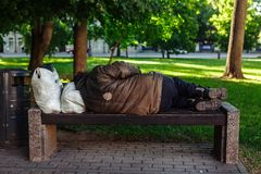 Homeless sleeping on a park bench. Lithuania royalty free stock photo