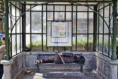 Homeless sleeping under a dirty tram shelter in Brussels stock photo