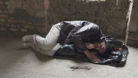 Homeless sleeps on garbage bag in abandoned building. Homeless sleeps on garbage bag on the cold ground in abandoned building. Bearded bum moves during sleeping stock footage