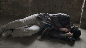 Homeless sleeps on garbage bag. On the cold ground in abandoned building. Bearded bum moves during sleeping. Portrait of young man wears dirty torn clothes stock video