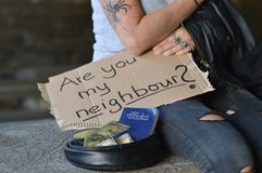 Homeless woman begging for money holding a sign stock images
