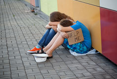 Homelessness. Homeless teenage boy and girl begging in street (The production scene; problem-free children play a role of beggars Stock Photography