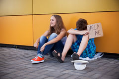 Homelessness. Homeless teenage boy and girl begging in street (The production scene; problem-free children play a role of beggars Stock Photo