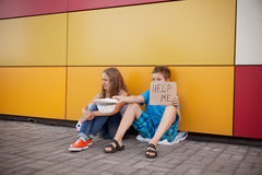 Homelessness. Homeless teenage boy and girl begging in street (The production scene; problem-free children play a role of beggars Stock Photos